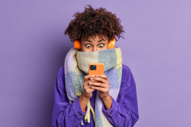 Stunned beautiful millennial girl with curly bushy hair stares at smartphone display scrolls news in internet wears wireless headphones velvet jacket scarf around neck.