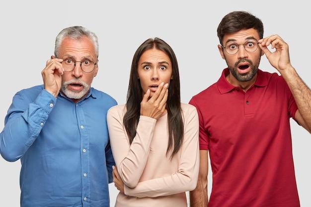 Fratello sbalordito, sorella e il loro anziano padre in posa contro il muro bianco