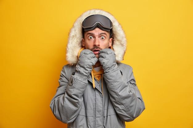 L'uomo adulto caucasico sbalordito fissa gli occhi spalancati indossa vestiti caldi per gli occhiali da sci della stagione fredda gode dell'hobby preferito e ha riposo attivo.
