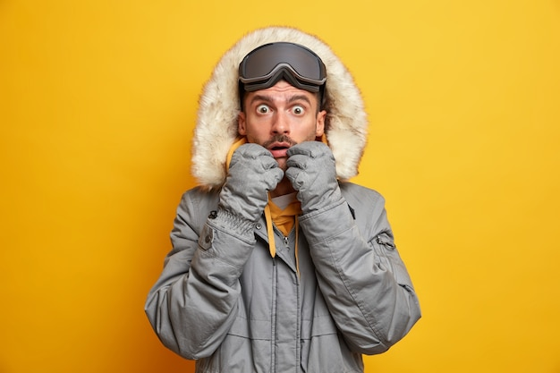 Ошеломленный взрослый мужчина кавказской национальности тупыми глазами смотрит на него в теплой одежде, в холодное время года, в лыжных очках, любит любимое хобби и активно отдыхает.