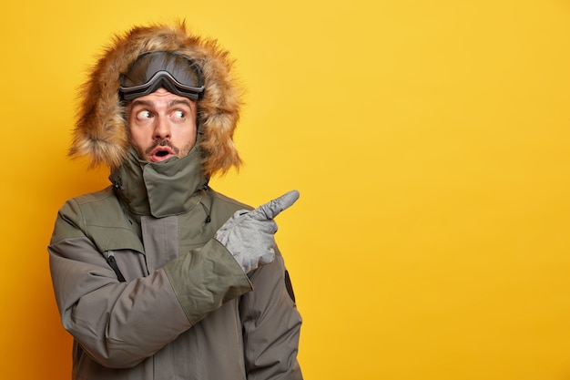 Stunned caucasian man in winter clothes points away on blank space with surprised expression goes skiing during cold day wears jacket and gloves enjoys chilly weather.