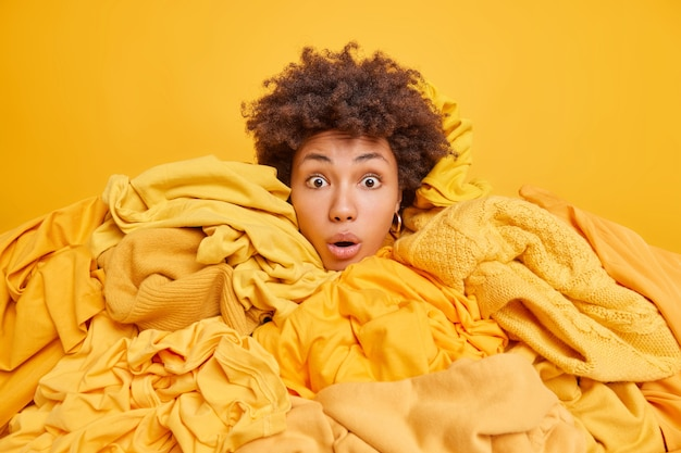 옷 더미에 머리가 박힌 곱슬머리 민족 여성은 중고로 판매되는 다양한 의류를 구매합니다. 노란색에 대한 그런 저렴한 가격 포즈는 믿을 수 없습니다