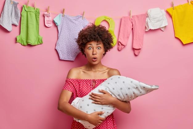 기절 한 곱슬 머리의 어머니가 유아 아기를 안고, 어린이의 심각한 질병을 발견하고, 입을 크게 벌리고, 포즈를 취합니다.