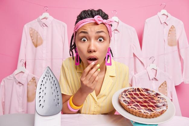 ドレッドヘアを持つ唖然とした暗い肌の女性の家政婦は、カメラに驚いて、ピンクの壁にさりげなく隔離された服を着て、自宅で忙しいアイロンをかけるおいしいパイを調理します