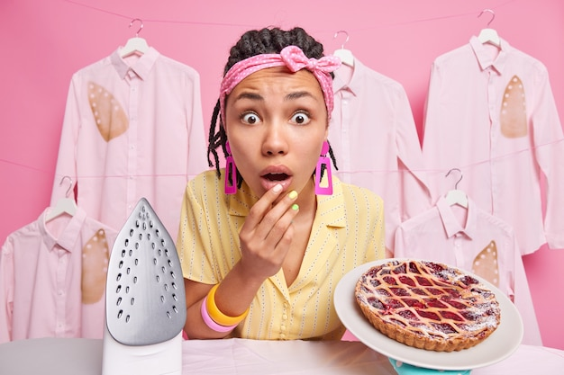 Stunned dark skinned woman housekeeper with dreadlocks stares surprised at camera cooks tasty pie busy ironing at home dressed casually isolated over pink wall
