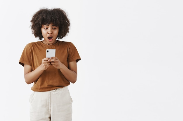 Ошеломленная, недовольная и шокированная афроамериканская женщина-подросток с кудрявыми волосами, задыхаясь и отвисшая челюсть от разочарования, смотрит на экран смартфона
