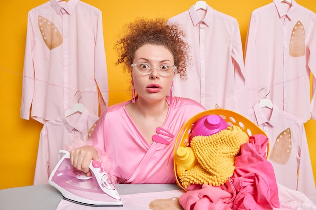 Stunned emotional curly haired female maid carries basket of laundry with detergents busy doing ironing wears transparent glsses and dressing gown poses against shirts on hangers. domestic chores