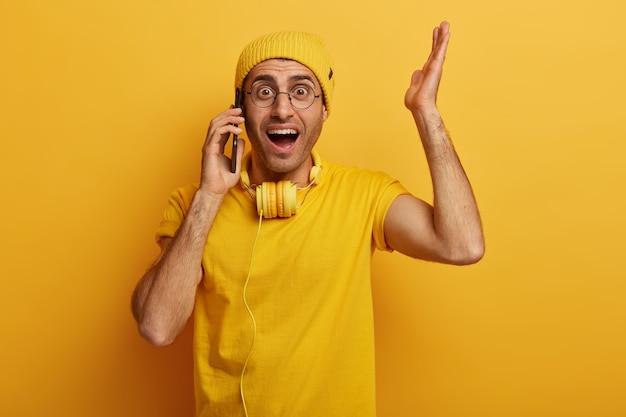 Ошеломленный эмоциональный парень поднимает руку, реагирует на шокирующую актуальность, разговаривает с кем-то по телефону, носит стильную желтую шляпу.