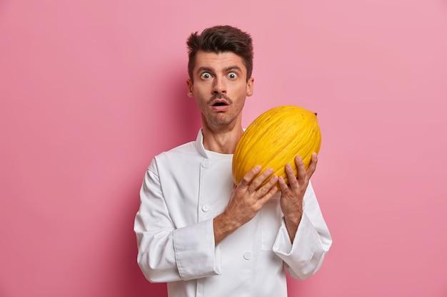 Stordito cuoco maschio emotivo tiene delizioso melone maturo dolce, andando a preparare gustosi dessert, guarda con shock