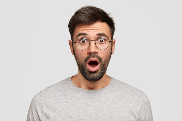 Stunned emotive bearded man keeps mouth widely opened, looks with bated breath