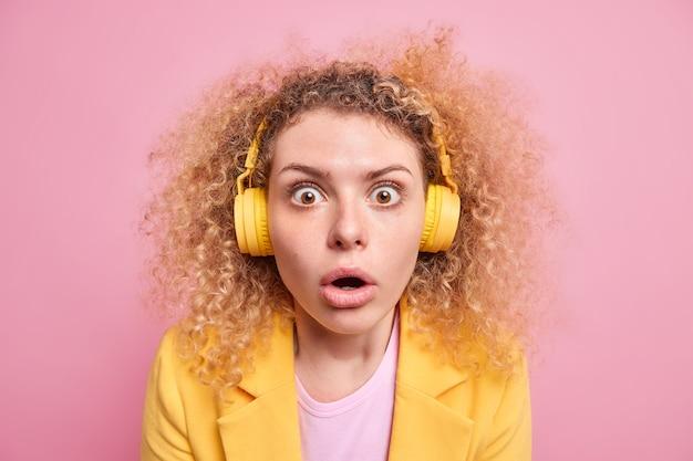 Ошеломленная эмоциональная молодая женщина с кудрявыми волосами слушает музыку в наушниках, вытаращив глаза, не может поверить в шокирующие новости, носит стильную одежду, изолированную на розовой стене. omg концепция.