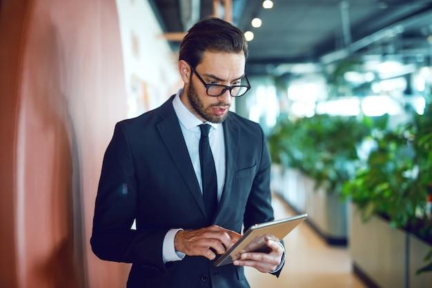 Ошеломленный красивый кавказский бизнесмен в костюме и в очках с помощью планшета, стоя в коридоре корпоративной компании.