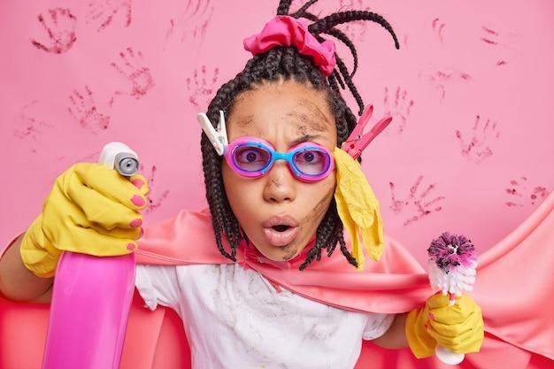 Ошеломленная домохозяйка с дредами держит ершик для унитаза с моющим средством и убирает комнату, одетая в костюм супергероя, заботится о чистоте, изолированной на розовой стене