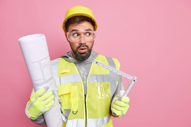 L'ingegnere del cantiere maschio stordito lavora con il progetto e il metro a nastro prepara il progetto di costruzione vestito con l'uniforme del casco di sicurezza sembra sorprendentemente lontano