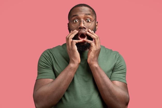 Ошеломленный мужчина широко открывает рот, держит руки на лице, реагирует на что-то ужасное, одет в повседневную одежду.