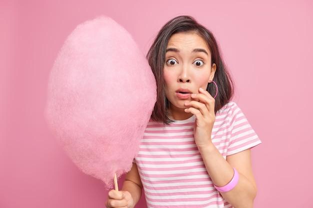 Ошеломленная испуганная брюнетка держит сладкую сахарную вату, удивленная услышать, что что-то удивительное узнает, сколько калорий она собирается съесть, носит полосатую футболку, изолированную над розовой стеной.