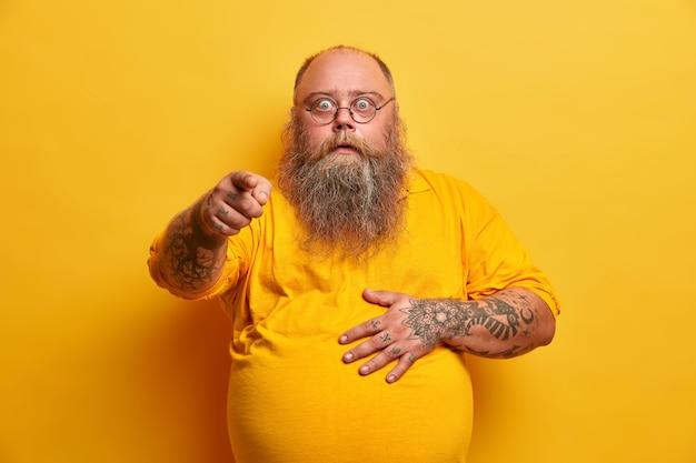 기절 한 충격을받은 수염 난 뚱뚱한 남자가 집게 손가락을 가리키고 배를 잡고, 예상치 못한 압도적 인 뉴스에 반응하고, 안경과 노란색 티셔츠를 입고, 실내 포즈를 취하고, 감동을 받고, 흥분을 느낍니다.