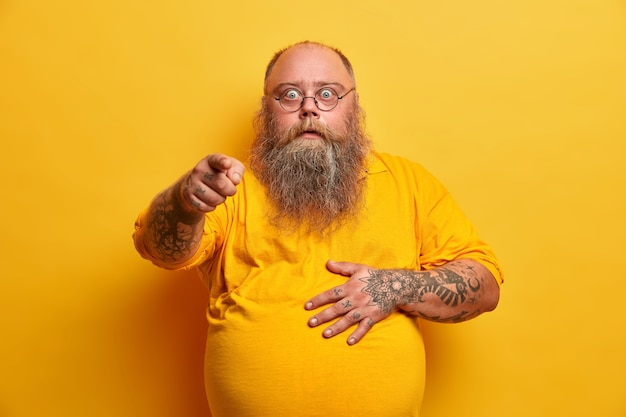 Stunned shocked bearded obese man points index finger and holds tummy, reacts to overwhelming unexpected news, wears spectacles and yellow t shirt, poses indoor, feels impressed, excited