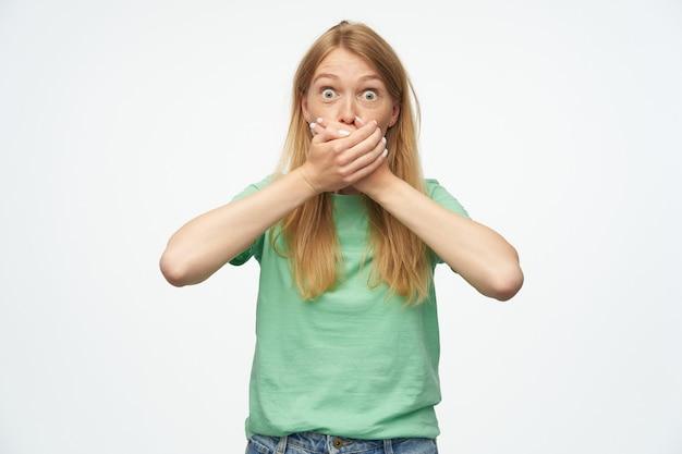 박하 tshirt에 주근깨가있는 충격을받은 여자는 손으로 입을 원추하고 흰색에 무서워 보인다.