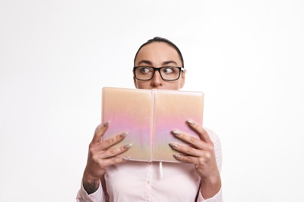 Stunned and surprised woman looking away and covering her mouth with pink book. isolated on white background with copy space