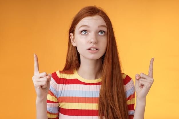Ошеломленная взволнованная молодая рыжая женщина, сверстница сосредоточена, указывая вверх указательными пальцами, смотрит сосредоточенно, возбужденно, задерживая дыхание, забавляется выступлением, стоя на оранжевом фоне, заинтригована и любопытна.