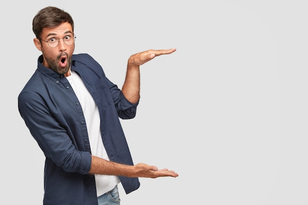 Stunned unshaven male with shocked facial expression gestures with hands, shows size or height of something, dressed in fashionable shirt, isolated over white wall, copyspace