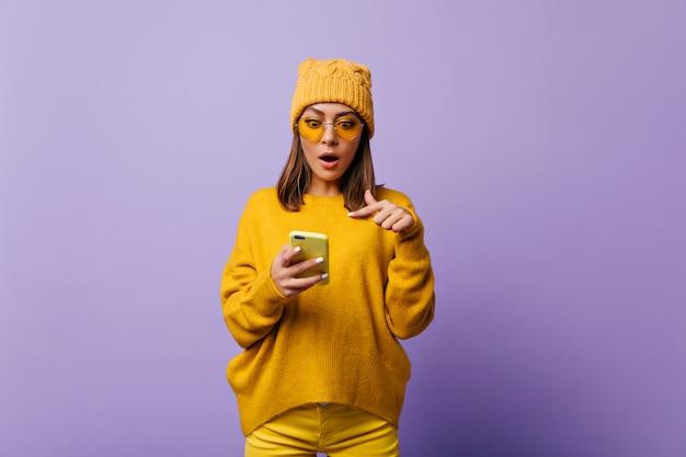 黄色いズボンと特大のセーターを着た唖然とした元気な女性は、スマートフォンの奇妙な電子文字に驚いています。紫色の壁に対する感情的なモデルの明るい肖像画