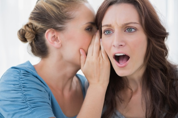 Stunned woman being told a secret by her friend