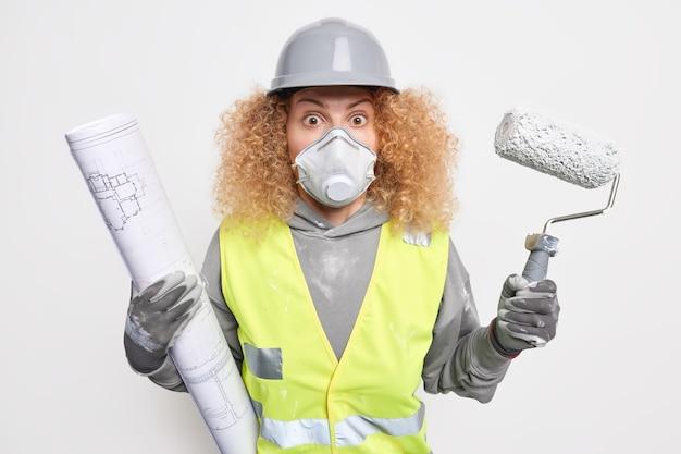 기절 한 여성 빌더는 미래의 건축 프로젝트를 위해 그림을 만듭니다. 페인트 롤러는 보호용 헬멧 얼굴 마스크와 작업복을 착용합니다.