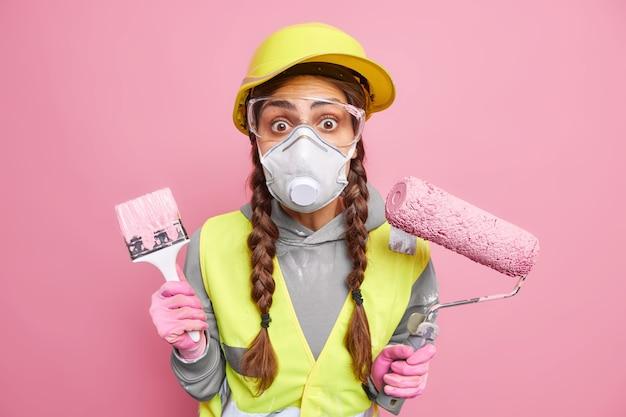 놀란 여성이 페인트 롤러와 붓을 들고 있는 diy 프로젝트에서 아파트를 다시 장식합니다