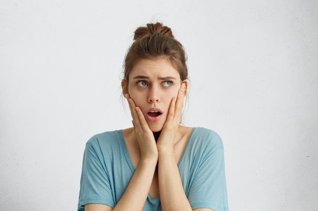 Stunned woman with hair knot wearing casual blue blouse holding hands on cheeks opening her mouth with surprise looking up