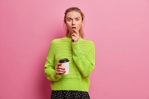 La giovane donna adulta sbalordita fissa scioccata, tiene in mano una tazza di caffè usa e getta, non riesce a credere ai suoi occhi, prende il tè del mattino a colazione, sussulta per la meraviglia, indossa un maglione lavorato a maglia verde