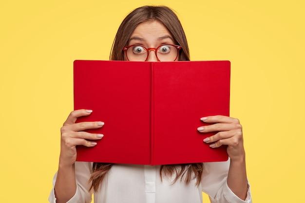 Ошеломленная молодая брюнетка в очках позирует у желтой стены