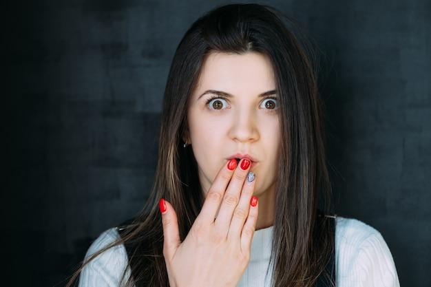 唖然とした若い女性の肖像画。開いた口を覆う手。 omgの表情。
