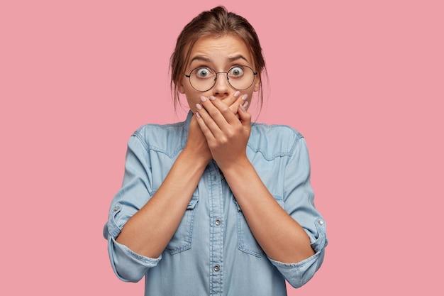 ピンクの壁にポーズをとって眼鏡をかけて唖然とした若い女性