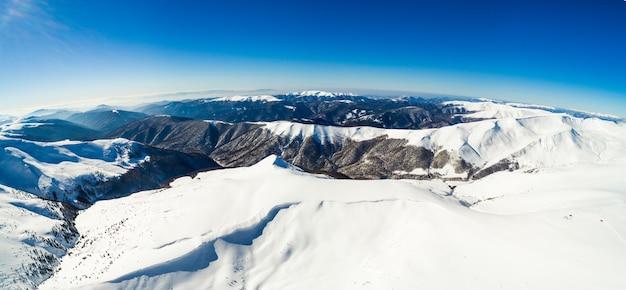 冬の晴れた凍るような日に山脈の見事な空中写真。ヨーロッパの冬の観光とスキー場の概念。テキストのペース