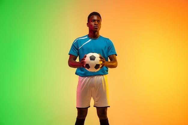 見事。アフリカ系アメリカ人の男性サッカー、ネオンの光の中でグラデーションスタジオの背景に分離されたアクションでトレーニングをしているサッカー選手。動き、行動、成果、健康的なライフスタイルの概念。青年文化