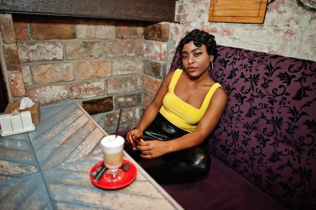 黄色のトップと黒い革のズボンを着た見事なアフリカ系アメリカ人の女性がコーヒーを飲みながらパブでポーズをとります。