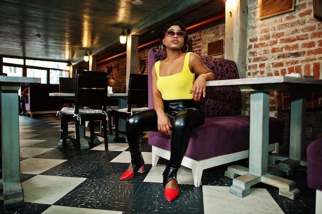黄色のトップと黒い革のズボンを着た見事なアフリカ系アメリカ人の女性がパブでポーズをとります。