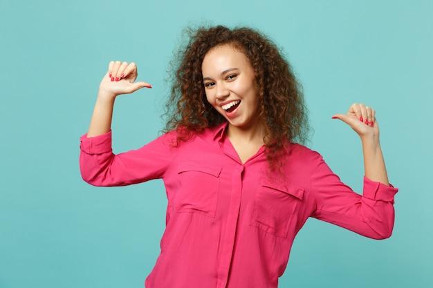 Splendida ragazza africana in abiti casual rosa che guarda la macchina fotografica, puntando i pollici su se stessa isolata su sfondo blu turchese in studio. persone sincere emozioni, concetto di stile di vita. mock up copia spazio.