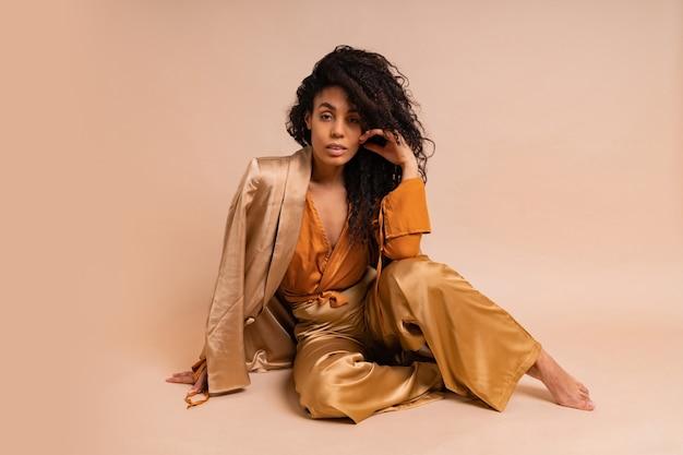Splendida modella africana con voluminosa acconciatura riccia in costume elegante in posa sul muro beige.