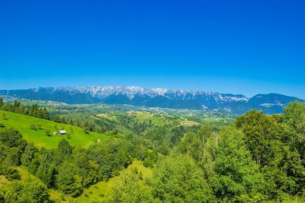 緑の野原とブラショフ近くの高い雪に覆われたピアトラクライウルイ山脈のある見事な高山の風景。古い木造家屋のある山の農場。ブラン、トランシルバニア、ルーマニア、ヨーロッパ。