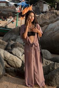 Сногсшибательная азиатская женщина в летнем наряде позирует на плече.