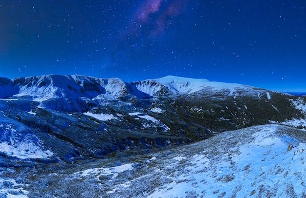 雪に覆われたモミの木と美しい冬の山の斜面のある見事な美しい自然の星空。手付かずの北の自然と雪に覆われた美しさの概念