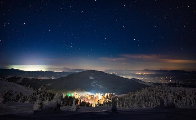 雲ひとつない星空の夜にゲレンデとモミがある冬のスキーリゾートの見事な美しい景色。田舎の冬と週末の休暇の概念。コピースペース
