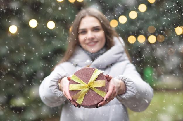 降雪時に通りでギフトボックスを保持している見事な金髪の女性。背景がぼやけている