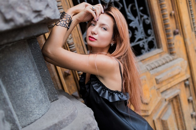 Stunning blonde elegant woman in black evening dress posing in city. red lips, red hairs,  unusual accessorizes .