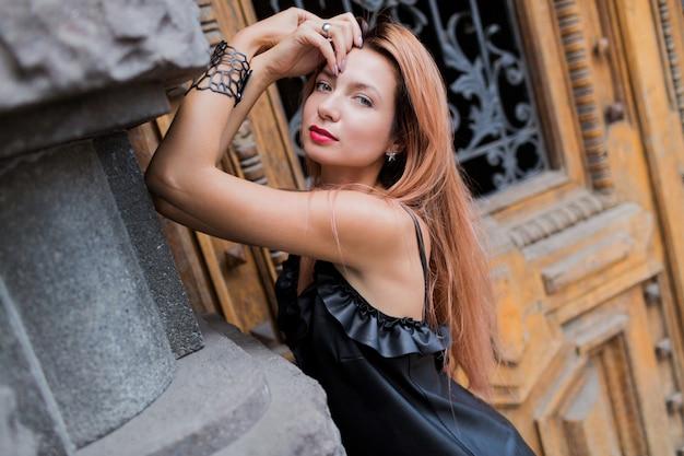 街でポーズをとって黒いイブニングドレスで見事な金髪のエレガントな女性。赤い唇、赤い髪、珍しいアクセサリー。