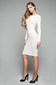 Stunning blonde girl in white simple dress