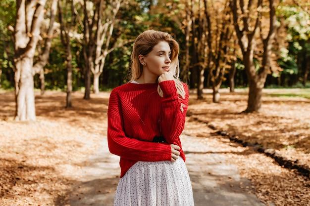 秋の森を遠くに見ているスタイリッシュな服を着た見事なブロンド。素敵な女の子は屋外で天気の良い日を楽しんでいます。